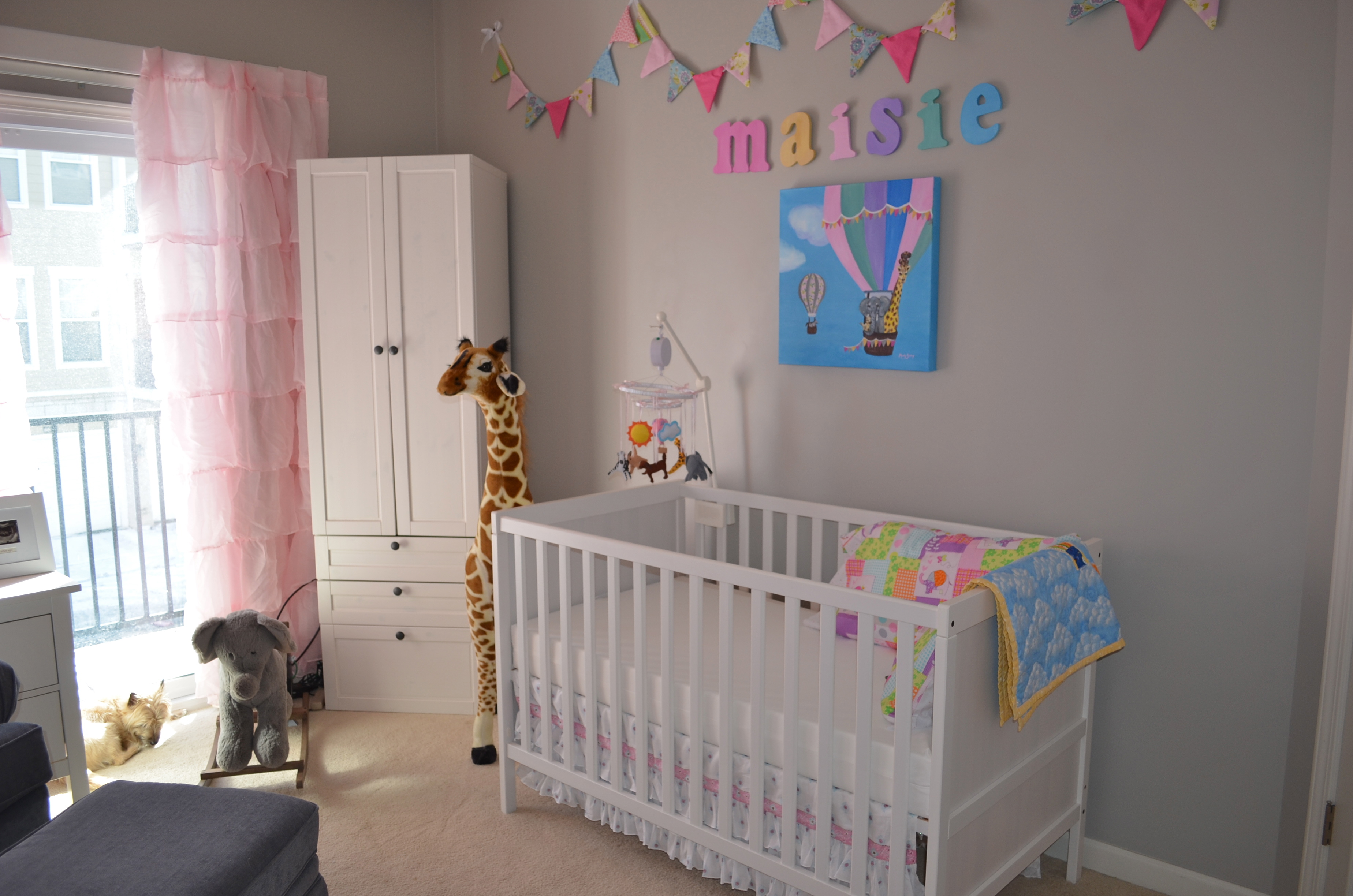 Grey, white, and pink are the main colors with flourishes of bright colors to make this nursery a happy place to be (hopefully even during middle of the night feedings).